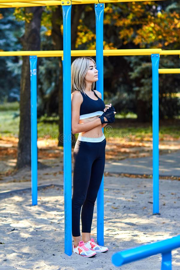 Sport girl. The girl is doing fitness exercises. Beautiful young sports woman doing exercises. A woman is training on a sports fie. Ld. Young beautiful girl in stock photography