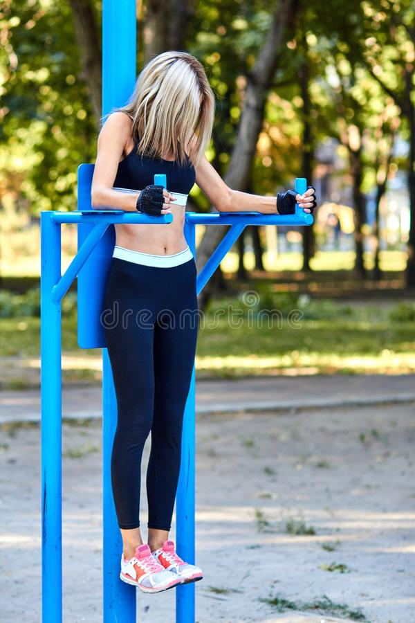 Sport girl. The girl is doing fitness exercises. Beautiful young sports woman doing exercises. A woman is training on a sports fie. Ld. Young beautiful girl in royalty free stock image