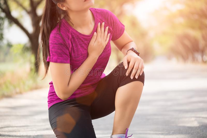 Sport girl have chest pain after jogging or running work out in park. Sport and Health care concept stock photography