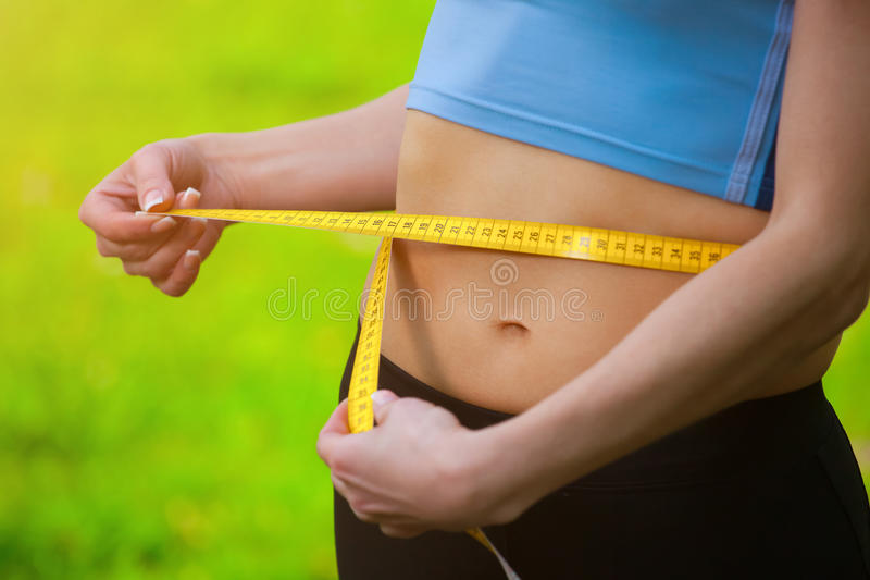 Sport girl measuring waist. royalty free stock images