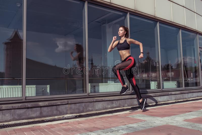 Sport girl runs summer city. Sportswear Leggings Top. Background showcase glass windows. Motivation fitness workout. Lifestyle. Free space text. Tanned slender royalty free stock image