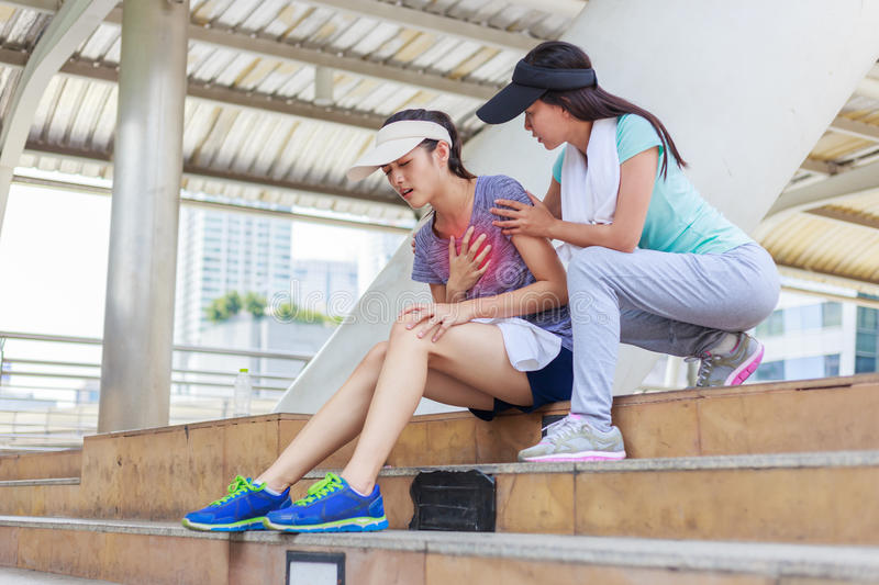 Sport girl try to help her friend who having symptomatic chest pain stock image