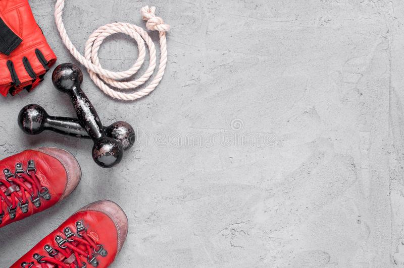 Sport glove, old shoes and small vintage dumbbell. Black background with copy space royalty free stock images