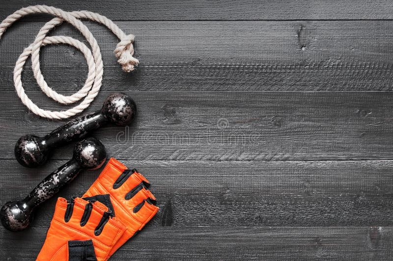 Sport glove, small vintage dumbbell and rope. Black background with copy space stock photos