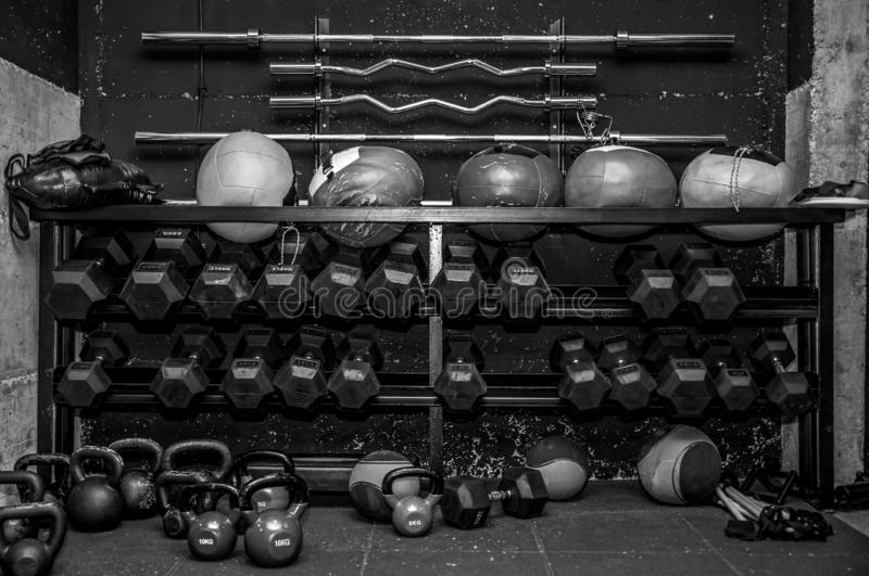 Sport gym equipment for fitness and body building workout training with barbell bars dumbbells kettlebells and balls on the stand royalty free stock photos