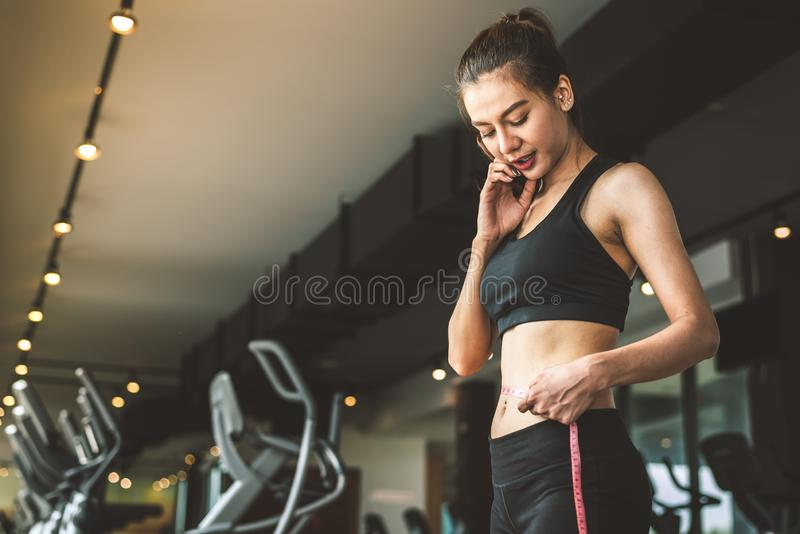 Sport happy slim woman using waist tape line in fitness gym sport club training center background. Success lifestyle of people royalty free stock images