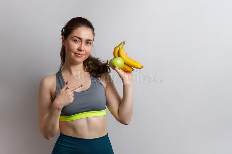 Sport and health. Beautiful athletic young woman in gym clothes with Apple and banana in her hands pointing at them with her royalty free stock image