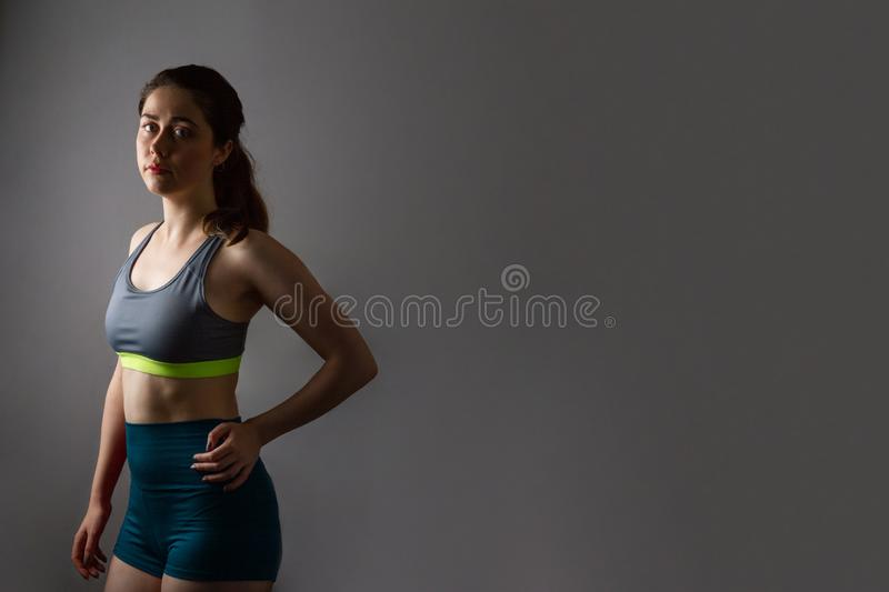 Sport and health. A beautiful athletic young woman in gym clothes, hands on hips, looking tired. Dark color. Copy space.  stock photos