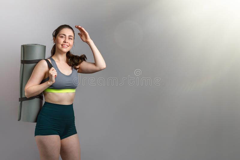 Sport and health. Beautiful athletic young woman in sportswear, holding a sports Mat, and looking raising her hand to her face. stock images
