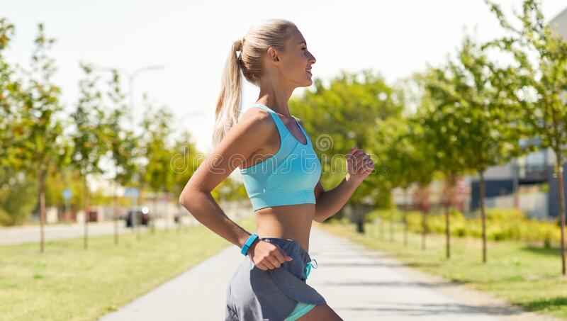 Smiling young woman running outdoors stock images