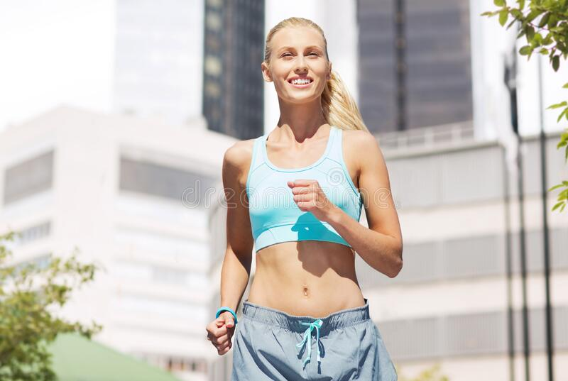 Smiling young woman running at city stock photography