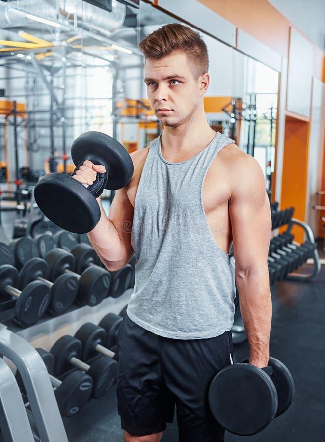 Sport, het bodybuilding, opleiding en mensenconcept - jonge mens met de spieren van de domoorverbuiging mensen die met domoren zi royalty-vrije stock afbeeldingen