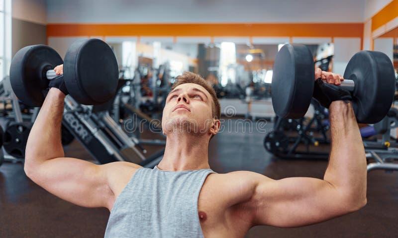 Sport, het bodybuilding, opleiding en mensenconcept - jonge mens met de spieren van de domoorverbuiging mensen die met domoren zi stock afbeelding
