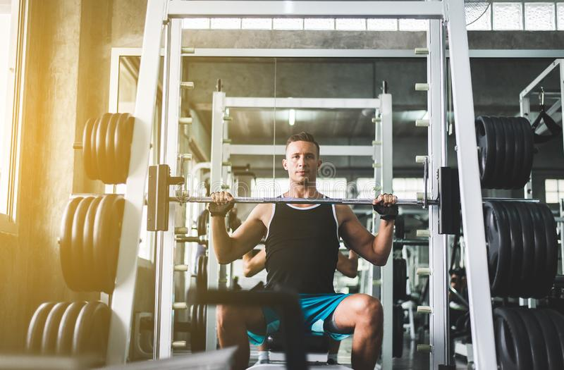 Sport het knappe mens oefent doen gewichtheffen, Dwars geschikt lichaam uit en spier in de gymnastiek stock foto
