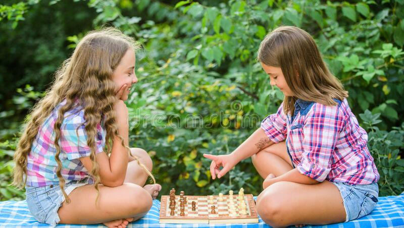 Sport and hobby concept. Little girls play chess. Sisters playing chess. Cognitive development. Intellectual game. Make. Decision. Smart children. Children play stock photography