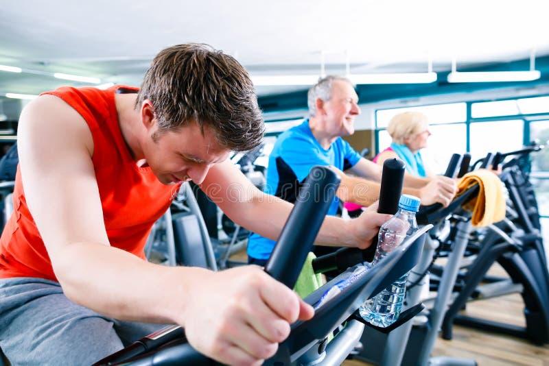 Sport i idrottshallen - folkrotering av kondition cyklar arkivfoton