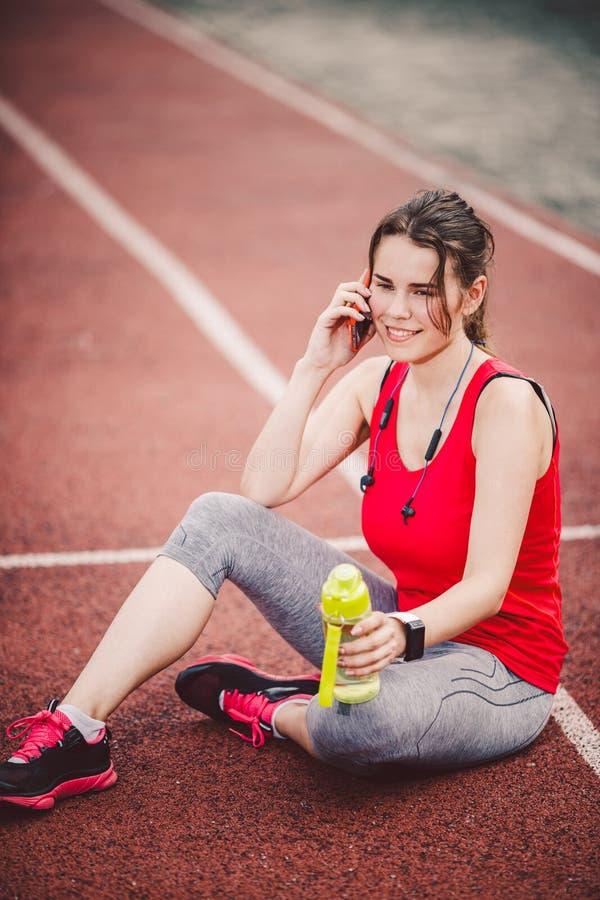 Sport i technologia Piękna młoda Kaukaska kobieta siedzi odpoczywać po treningu podczas bieg przy stadium z ponytail, czerwień t obraz royalty free