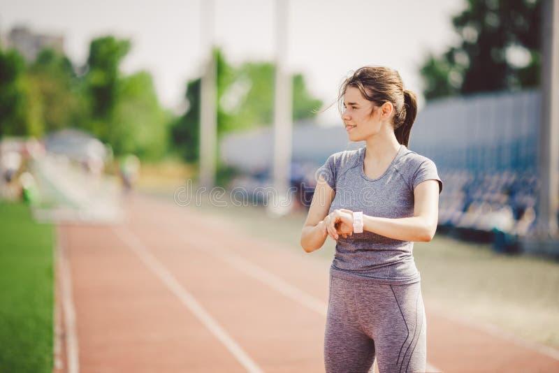 Sport i technologia piękni potomstwa whiteskinned kobieta z ponytail przy działającym stadium przed treningiem używa sporty mądrz zdjęcie stock