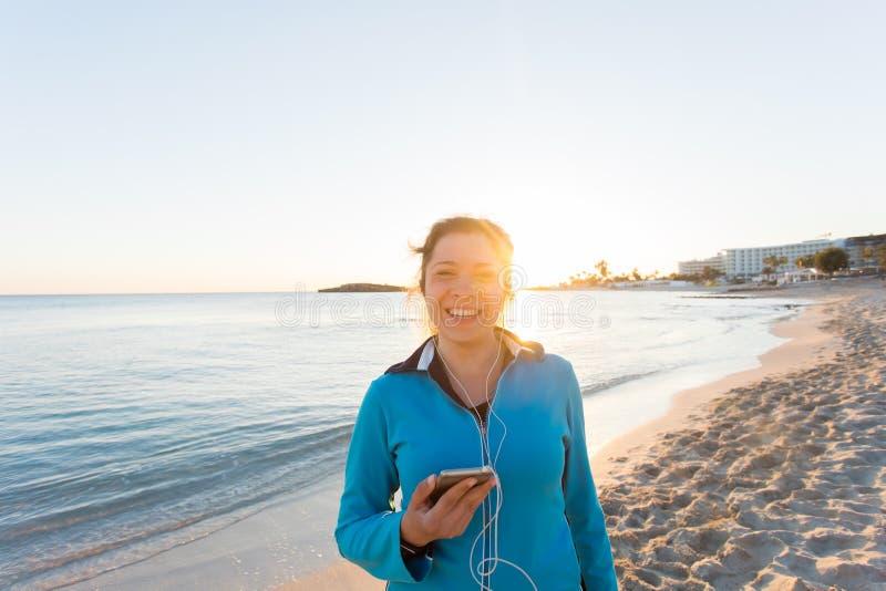 Sport im Freien, Eignungsgerät und Leutekonzept - lächelnde weibliche Eignung, die Smartphone mit Kopfhörern hält stockbild