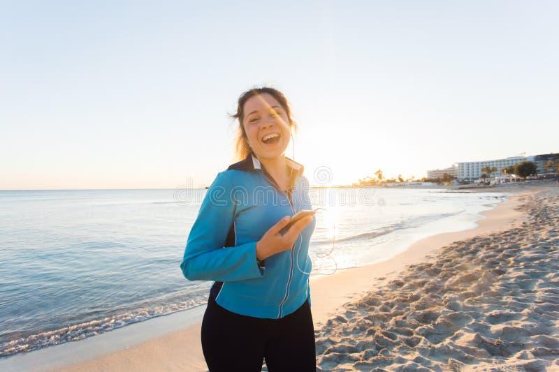Sport im Freien, Eignungsgerät und Leutekonzept - lächelnde weibliche Eignung, die Smartphone mit Kopfhörern hält lizenzfreie stockfotos