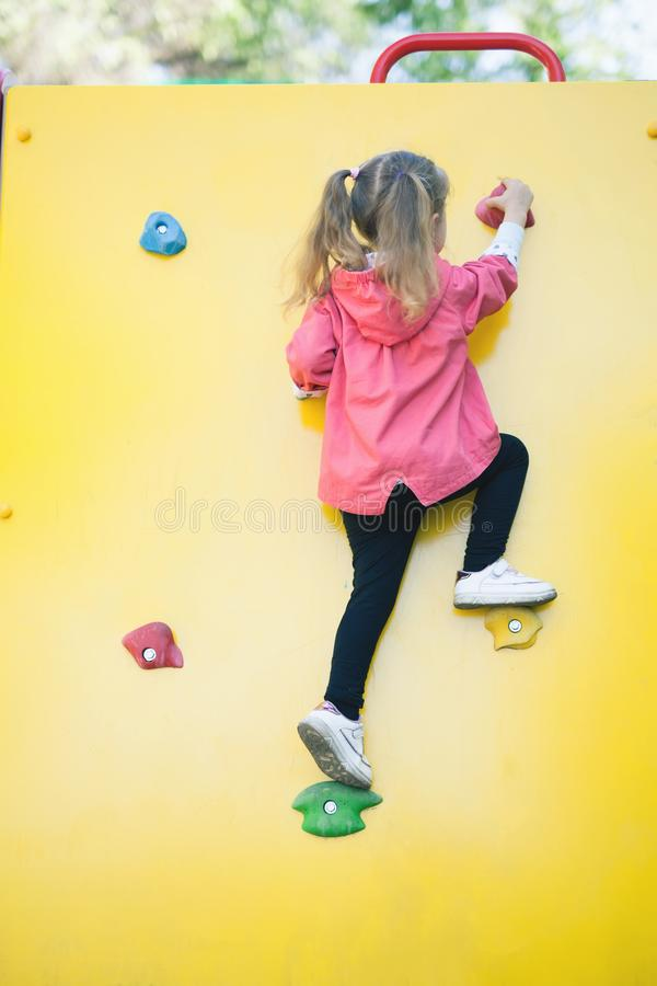 Sport image of climbing little girl to top of wall royalty free stock images