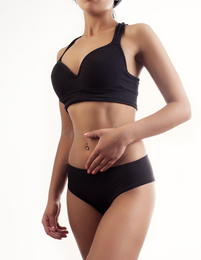 Sport jonge vrouw met pijn die zich tegen muur in fitness st bevinden stock foto