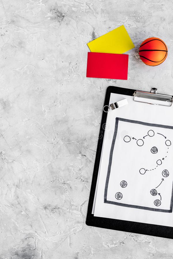 Sport judging concept. Basketball referee. Tactic plan for game, basketball ball, red and yellow cards, whistle on stone stock image