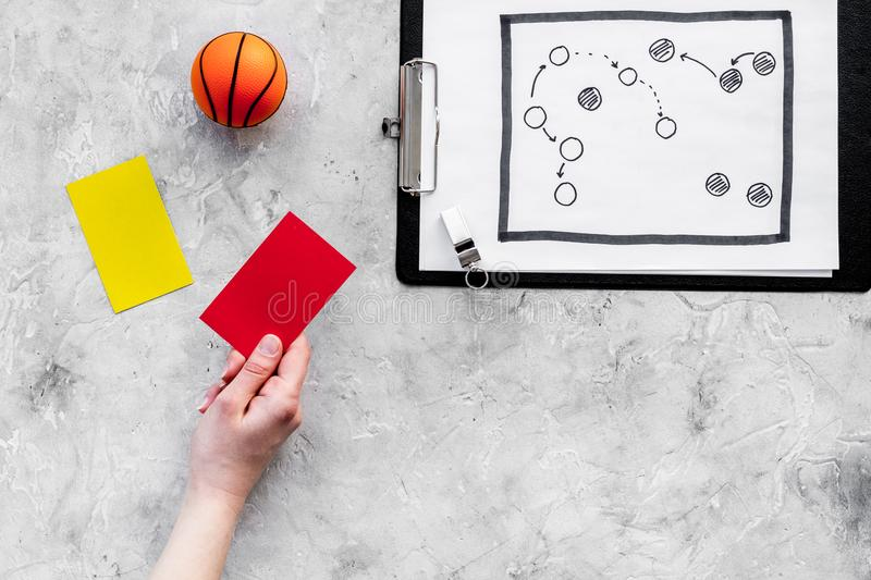 Sport judging concept. Basketball referee. Tactic plan for game, basketball ball, red and yellow cards, whistle on stone stock images