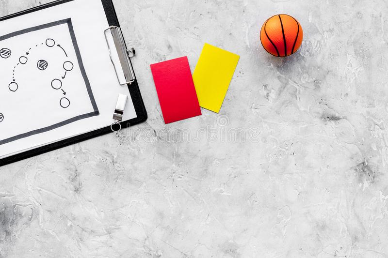 Sport judging concept. Basketball referee. Tactic plan for game, basketball ball, red and yellow cards, whistle on stone royalty free stock photos