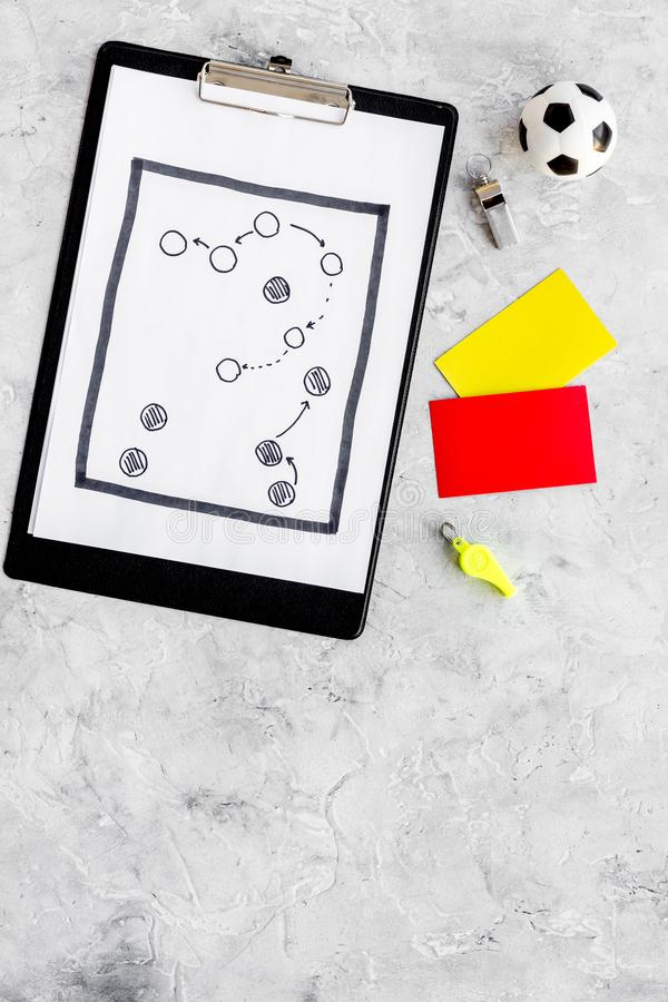 Sport judging concept. Soccer referee. Tactic plan for game, football ball, red and yellow cards, whistle on stone royalty free stock photo