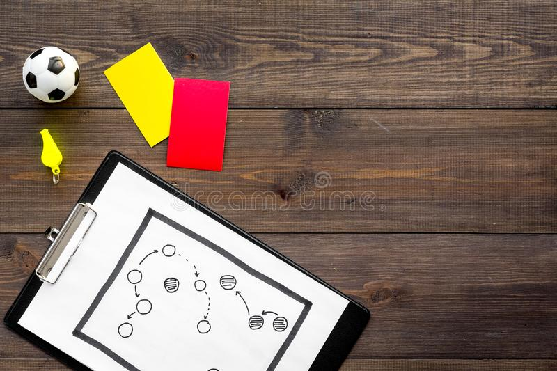 Sport judging concept. Soccer referee. Tactic plan for game, football ball, red and yellow cards, whistle on wooden royalty free stock photos