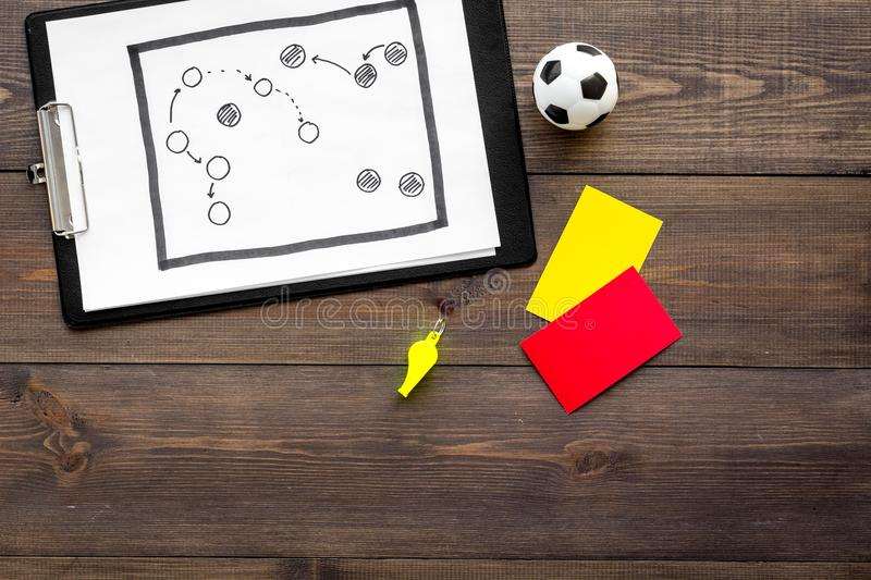 Sport judging concept. Soccer referee. Tactic plan for game, football ball, red and yellow cards, whistle on wooden royalty free stock photo