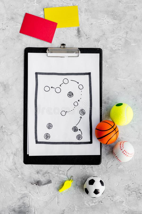 Sport judging concept. Sport game referee. Tactic plan for game, balls, red and yellow cards, whistle on stone royalty free stock photo