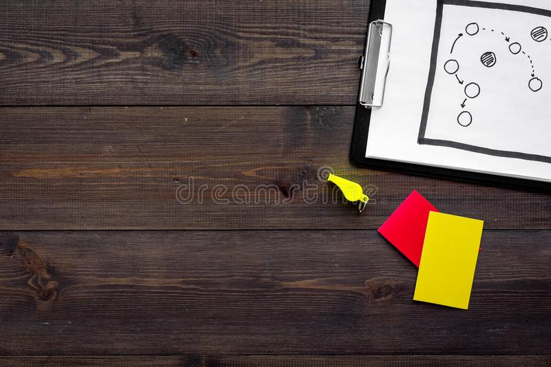 Sport judging concept. Tactic plan for game, red and yellow cards, whistle on wooden background top view copy space royalty free stock photo