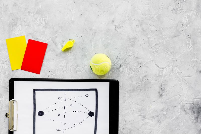 Sport judging concept. Tennis referee. Tactic plan for game, tennis ball, red and yellow cards, whistle on stone royalty free stock photos