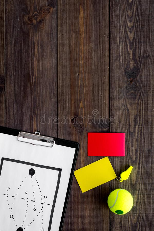 Sport judging concept. Tennis referee. Tactic plan for game, tennis ball, red and yellow cards, whistle on wooden stock photo