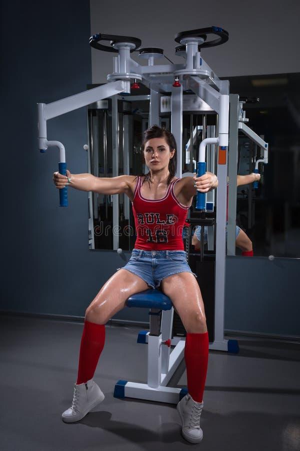 Sport kobieta robi ćwiczeniom na władza stażowym aparacie w gym W podsyca Młoda dziewczyna robi ćwiczeniu na stażowym appara fotografia royalty free