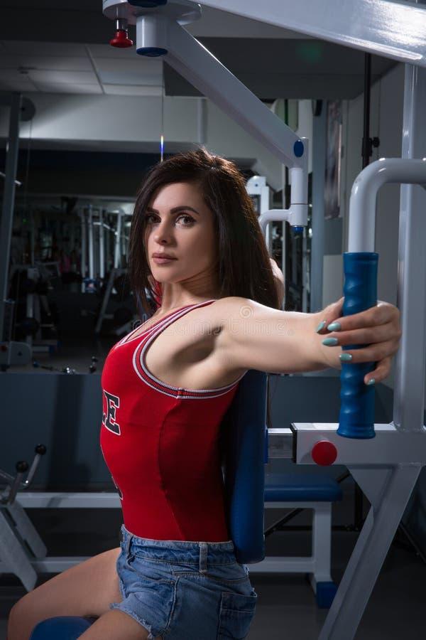 Sport kobieta robi ćwiczeniom na władza stażowym aparacie w gym W podsyca Młoda dziewczyna robi ćwiczeniu na stażowym appara fotografia stock