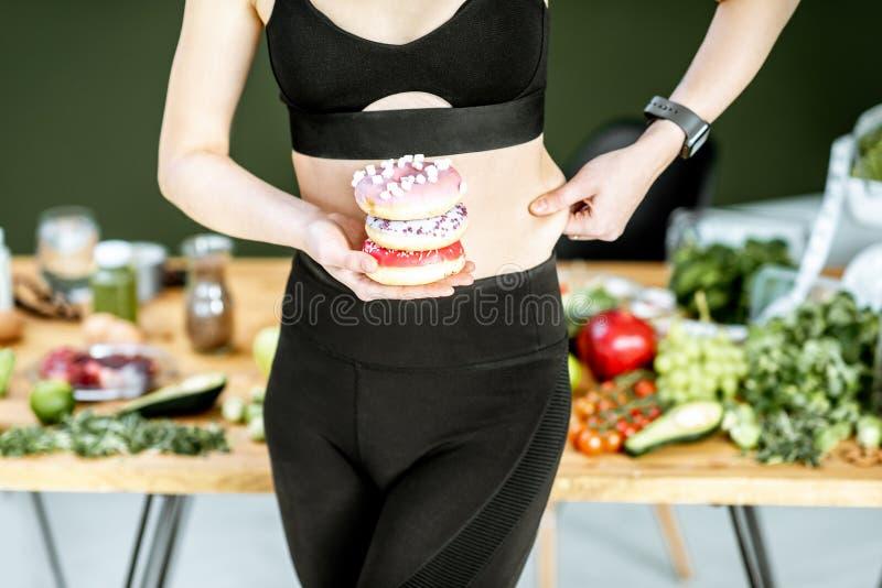 Sport kobieta z donuts i zdrowym jedzeniem obrazy royalty free