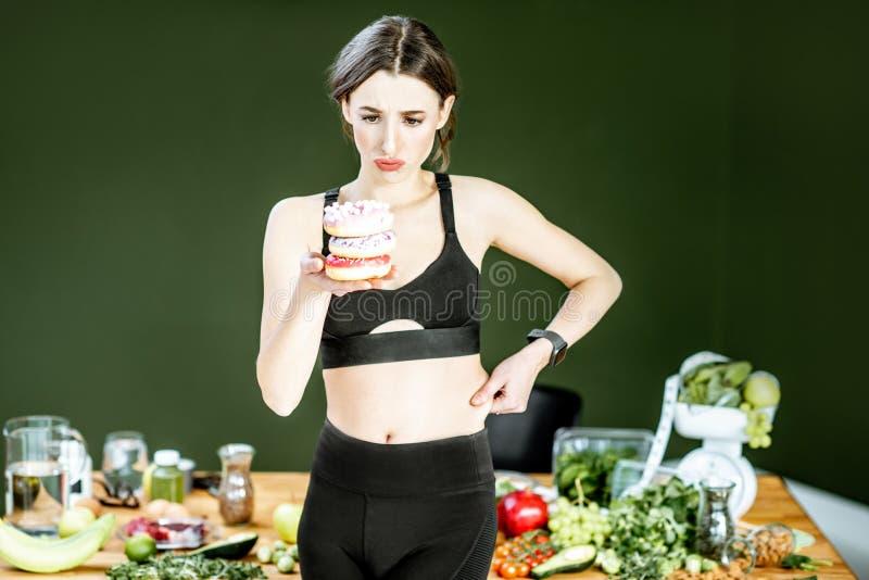 Sport kobieta z donuts i zdrowym jedzeniem zdjęcie royalty free