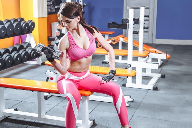 Sport, kondition, bodybuilding, tyngdlyftning och folkbegrepp - ung kvinna med hanteln som böjer muskler i idrottshall royaltyfria foton