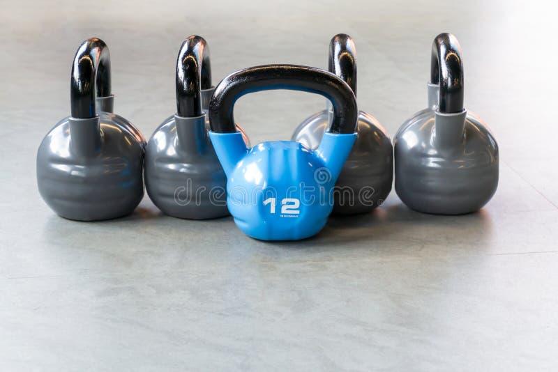Sport-, kondition- eller bodybuildingbegreppsbakgrund Sammansättningen av järnkettlebells på golvet i idrottshallen royaltyfria bilder