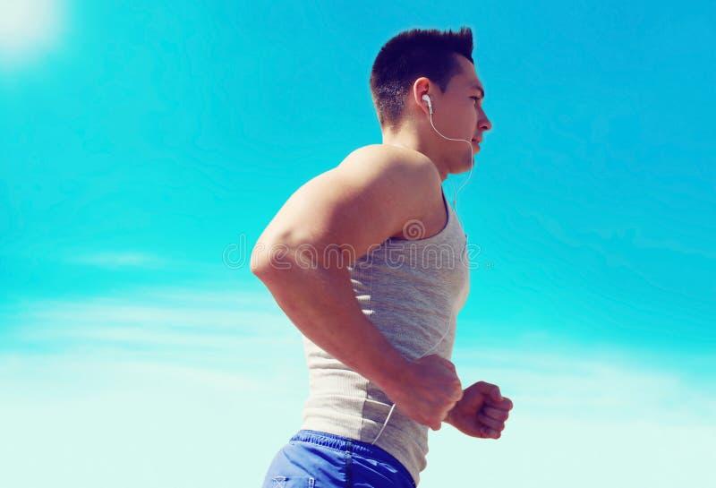 Sport, kondition, genomkörare och sunt livsstilbegrepp - idrottsman nenmanspring lyssnar till musik i hörlurar över blå himmel royaltyfri fotografi