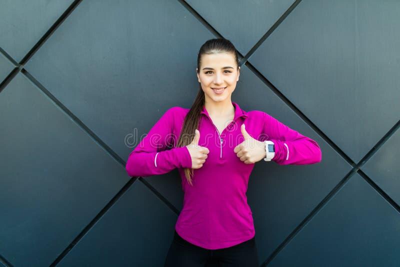 Sport, kondition och folkbegrepp Den lyckliga le sportive visningen för ung kvinna tummar upp över svart streeväggbakgrund royaltyfri fotografi