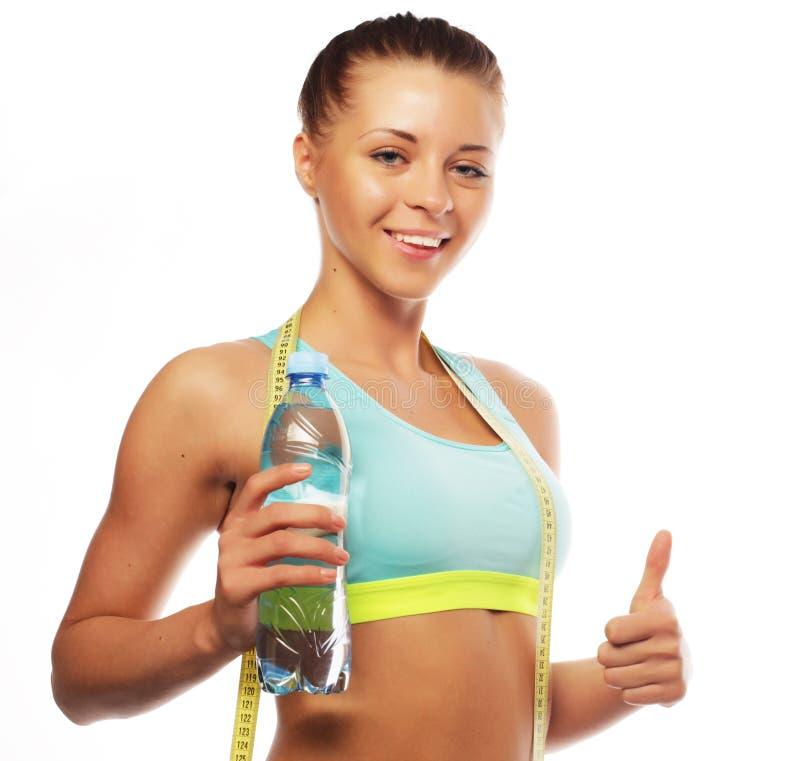 Sport, kondition och folkbegrepp: Ung lycklig le kvinna i sportswear med vatten, arkivfoto