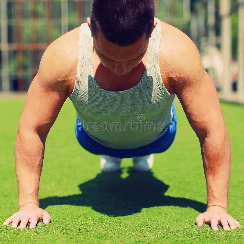 Sport-, kondition- och genomkörarebegrepp - idrottsman som gör push-UPS arkivbild