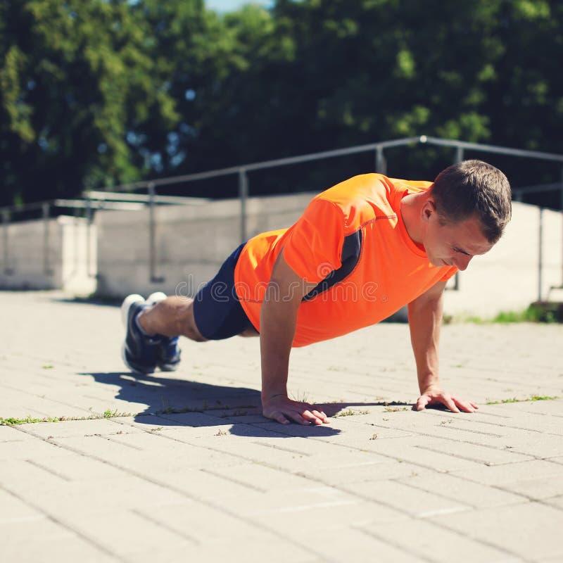 Sport-, kondition- och genomkörarebegrepp - idrottsman som gör push-UPS fotografering för bildbyråer