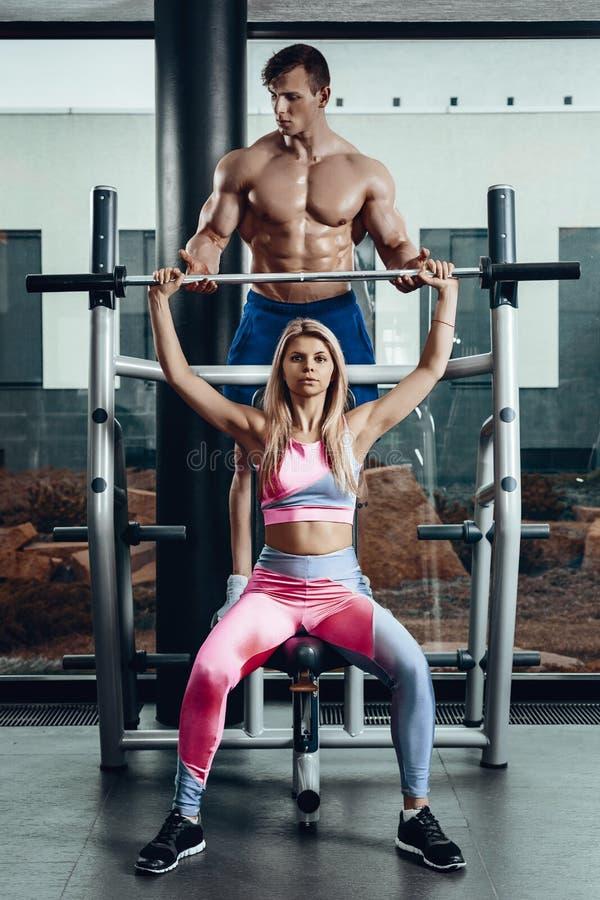 Sport, kondition, teamwork, bodybuilding och folkbegrepp - ung kvinna och personlig instruktör med att böja för skivstång arkivbild