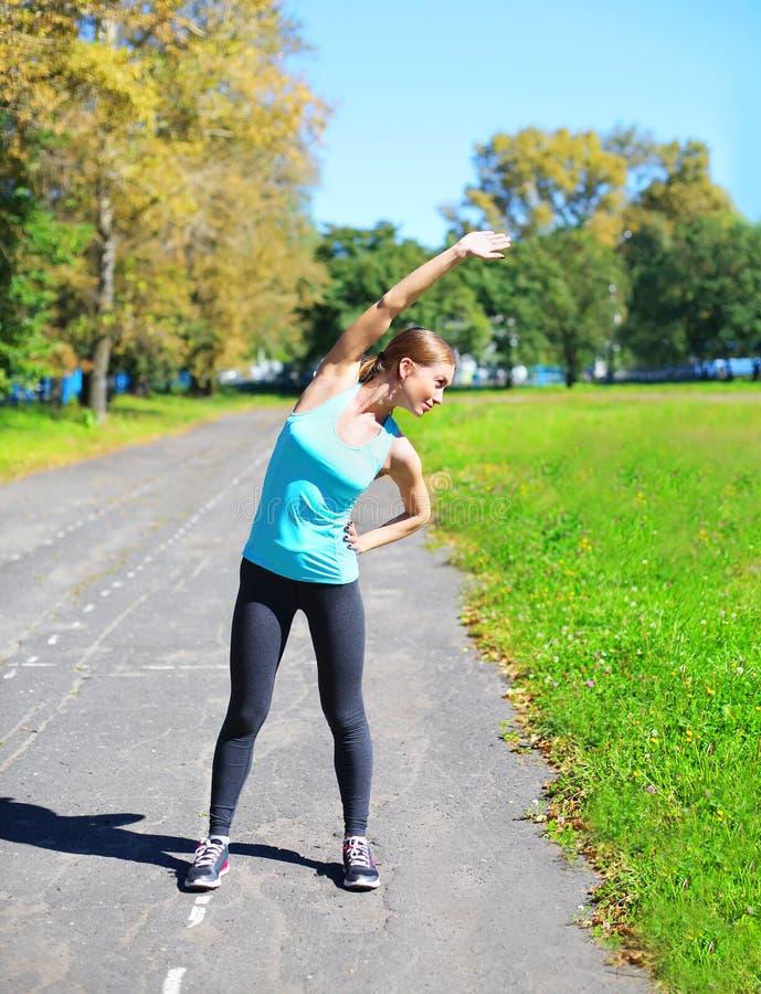 Sport konditionbegrepp - kvinna som gör sträcka övning och förbereda sig till den inkörda staden royaltyfria bilder