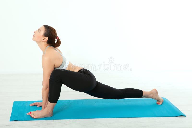 sport Konditionyogakvinna Den härliga medelåldersa kvinnan som gör yoga, poserar Begreppsfolket är genomköraren i yoga som in utb royaltyfri fotografi